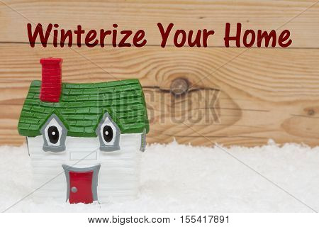 Your house in the winter season A green and red house on snow and a weathered wood background with text Winterize Your Home