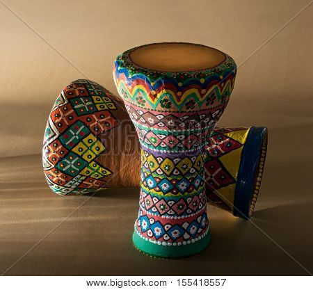 Two decorated colorful pottery goblet drums (chalice drum tarabuka darbuka) on background of wooden table with vanishing shadow lines. Low light studio shot