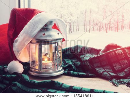 Winter background. Christmas and New Year winter still life -lantern with candle and Santa hat on the wooden windowsill and winter park outdoor. Festive Christmas and New Year winter still life.Christmas and New year winter concept