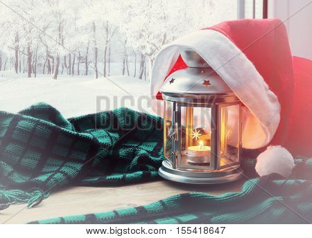 Christmas and New Year winter background-lantern with candle and Santa hat on the windowsill and winter nature outdoors. Festive Christmas and New Year winter still life.Christmas and New year concept