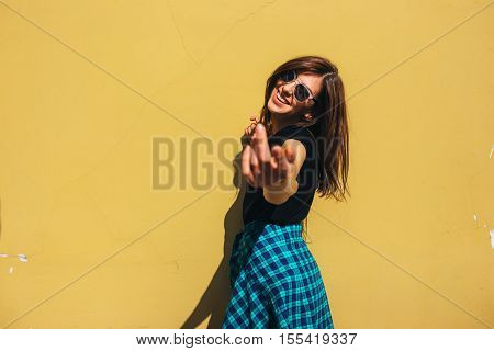 Brunette girl in rock black style, standing against yellow wall outdoors in the city street.