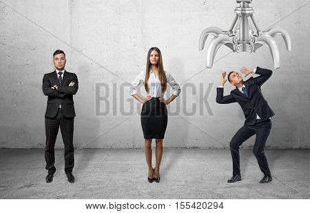 A confident businessman and businesswoman standing straight and a scared businessman shielding himself with his hands from the giant mechanical claw above him, all on the grey background. Business and management. Recruitment and competition.