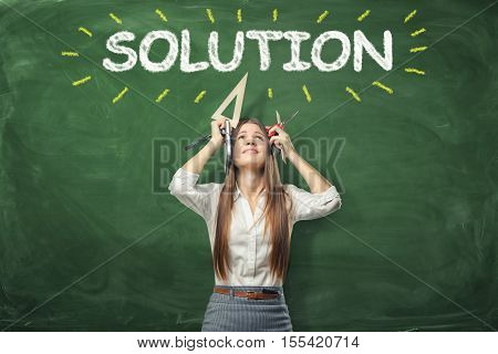A young woman holding different office supplies in her hands and standing under the word 'solution' written above her head. Solving a problem. Never give up. A way out of the difficult situation.