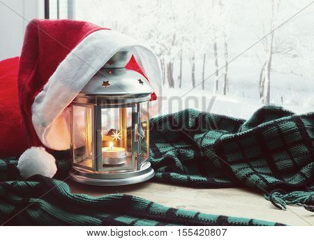 Festive tranquil Christmas still life -lantern with candle and Santa Christmas hat on the windowsill and winter park outdoor. Concept of Christmas and New Year.Christmas and New year still life. Christmas background. Holiday Christmas still life