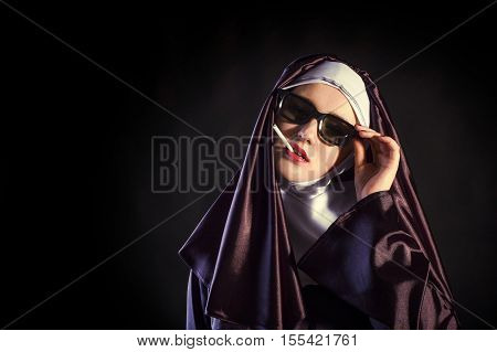 Nun in glasses is smoking. black background