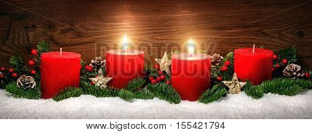 Low-key studio shot of elegant advent decoration with fir branches on snow and tow burning red candles dark wood background