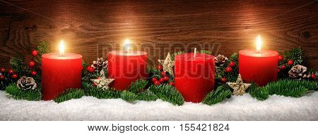 Low-key studio shot of elegant advent decoration with fir branches on snow and three burning red candles dark wood background