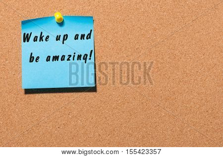 Wake Up and Be Amazing message text written on blue sticker pinned at cork notice board with empty space for message.
