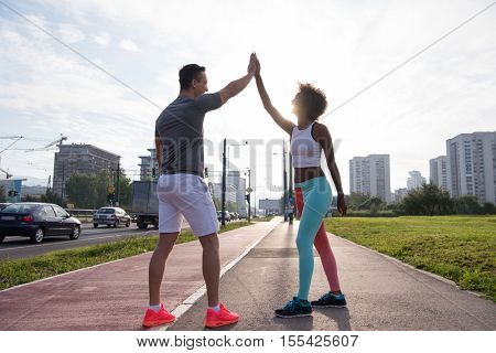 couple congratulating on morning run ginis young sporty mixed rase couple congratulating with hand five after successful morning jogging