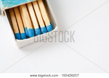 Blue matchsticks in vintage matchbox on white. Macro view matches in opened box,
