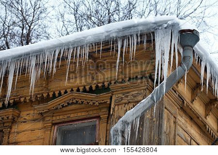 Frozen mysterious mansion with water pipe and frozen icicles on the roof, top floor wooden mansion. Icy weather winter