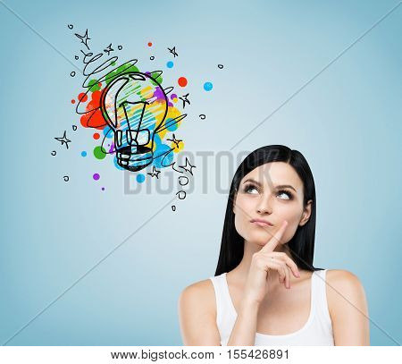 Close up of girl in white tank top looking at colorful light bulb sketch drawn on blue wall. Concept of good idea