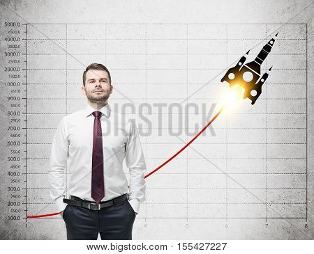 Proud businessman in red tie is standing near concrete wall with graph and rocket sketch on it. Concept of launching a new project.