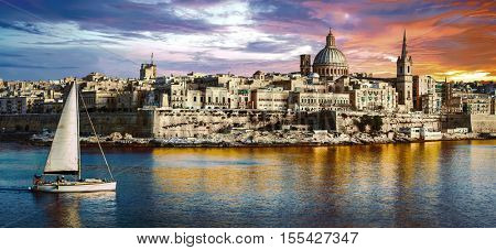 panoramic view of Valetta over sunset and with a sail boat. Malta