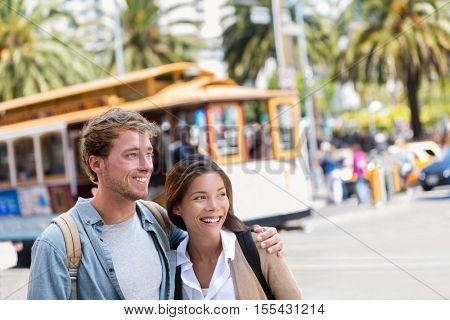 San Francisco city travel couple tourists people lifestyle. Young interracial students on city street looking away with cable car railway system in the background, popular attraction in San Francisco.