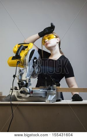 Tired worker. Young beautiful woman in overalls and glasses with disk saw.