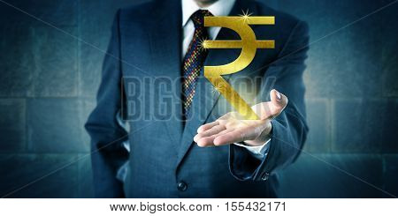 Businessman offering a golden Indian rupee symbol in the open upward facing palm of his left hand. Business metaphor and financial concept for national currency interbank market and investment.