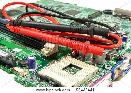 Multimeter probe on the motherboard in a workshop