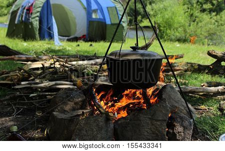 Cooking outdoors. Cauldron on a fire in the forest. On the background of the tent a river and trees.