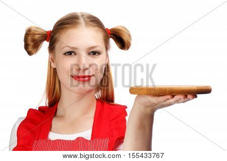 Young beautiful attractive smiling housewife in bright red apron with funny ponytails holding wooden cutting board isolated on white background. Close up.
