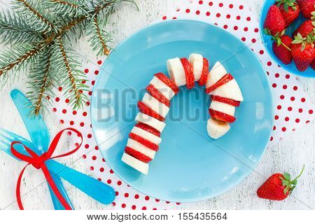 Funny edible candy cane - banana and strawberry candy cane on plate. Christmas treats for kids