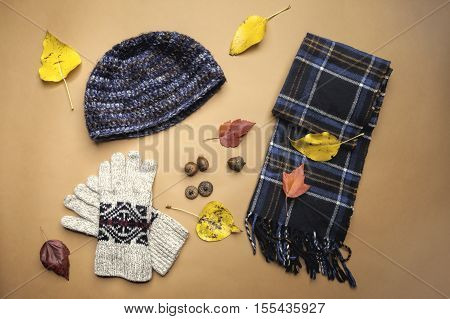 A display of warm weather outerwear that consists of gloves wool knit cap and a scarf.
