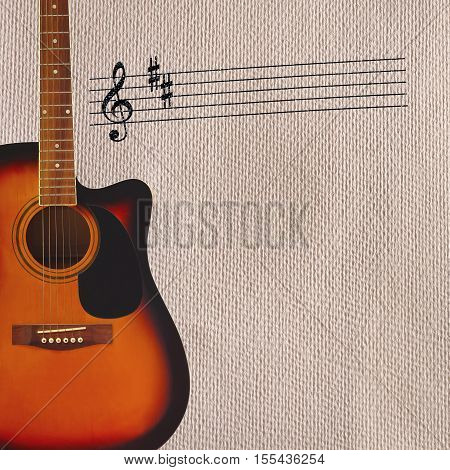 Stave and acoustic sunburst guitar on the left side of the rough cardboard background.