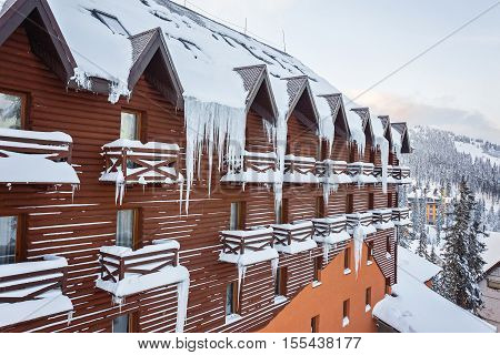 Long and dangerous icicles on a house roof over a balcony