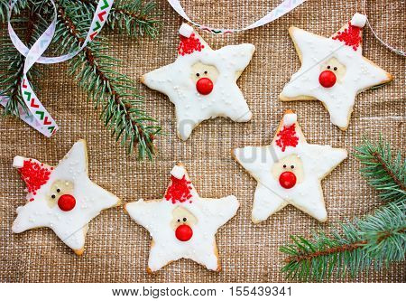 Christmas gingerbread cookies with icing shaped santa claus for gift funny edible santa recipe for kids holiday Christmas baking background top view