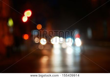 NIht in the city blurred shot. Cars in the street with reflections of carlights in asphalt road surface shot with space for text, copyspace, vintage color, dark sky.