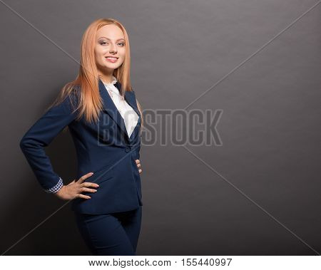 Beautiful business woman posing with her hands on hips isolated on grey background. Happy red haired woman smiling for camera in studio.
