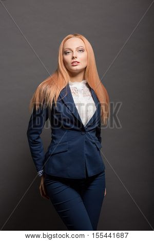 Portrait of executive serious business woman posing for photographer isolated on grey background in studio. Business concept.