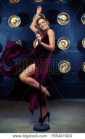 Mid shot of carefree singer in fluttering long dress breaks into song with vintage microphone. Elegant young female singer in black dress smiling