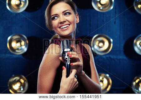 Close-up of elated young woman singing in a silver vintage microphone wearing vinous evening dress. Using studio microphone and posing at the camera