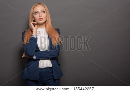 Portrait of professional model with red hair posing for photographer in studio. Pretty woman in navy blue business suit looking away.