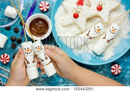 Creative idea to treat kids for Christmas party - homemade marshmallow pops shaped cute snowman santa claus cookies. Children's hands hold funny edible snowman top view