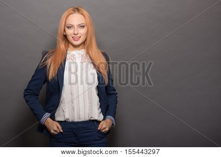 Portrait of happy smiling red haired young model woman posing with her hands in pockets isolated on grey background in studio. Fashion or vogue concept.