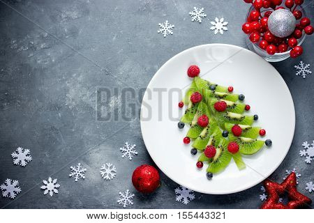 Funny edible Christmas tree Christmas breakfast idea for kids. Beautiful Christmas and New Year food background top view blank space for text