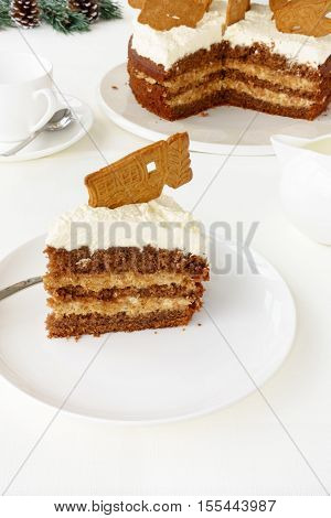 A slice of Gingerbread cake (Spekulatius Torte) with Spekulatius cookie as decoration on top traditionally eaten in winter and Christmas season. The cut cake and Christmas decoration in the background.