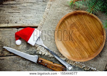 Christmas table place setting empty wooden plate cutlery on wooden background top view