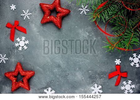 Christmas background with decorations snowflake star ribbon bow and Christmas tree branch on concrete gray background top view empty space for text
