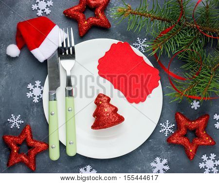 Christmas table setting place with festive decorations and empty greeting card. Christmas dinner background top view