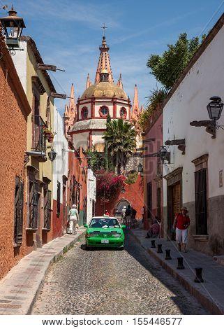 SAN MIGUEL DE ALLENDE MEXICO - MARCH 26 2011: Green taxi in front of Parroquia de San Miguel Arcangel. The gothic facade of this local parish church was inspired by Gaudi Sagrada Familia.