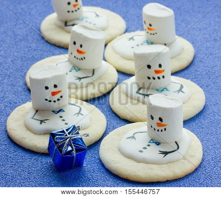 Melting Snowman Christmas Cookie on blue background