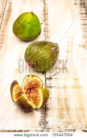 Whole figs and one fig sliced in half on top of a rustic wooden table