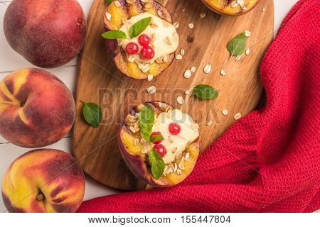 Grilled peaches with yogurt gooseberries and mint leaves on wooden table