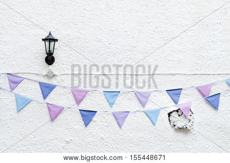 Colorful Party flags bunting hanging on white wall background with wall lamp light. Minimal hipster style design.
