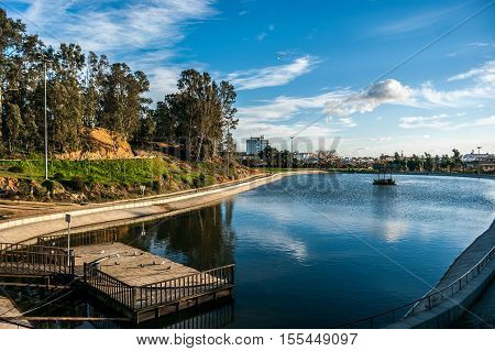 Lake of the park Moret with the blue sky and white clouds. The park is the biggest green space of the city of Huelva in Spain