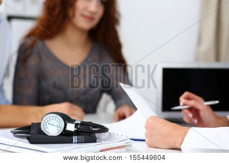Medical manometer lying on table while doctor consult young couple patients closeup. Motherhood and child delivery new life or abortion family therapeutist hospital and clinic concept.
