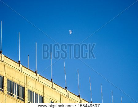 crescent moon visible in blue sky in the day with no clouds.  Building with antaenna.  The moon and the TV tower are located on a clear blue sky day. Two single object. Abstract landscape. Clear sky. A natural phenomenon. Moon in the sky during the day. I